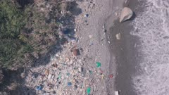 Beach covered in plastic marine debris causing climate change and environmental problems. Top down aerial drone view