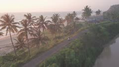 A Motorcycle Crossing A Small Concrete Road Next To The Varkala Beach Under The Sunset In Kerala, India. -aerial shot
