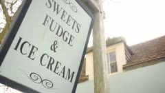 Sweets fudge and ice cream shop sign moving in the stormy wind, Dorset, England