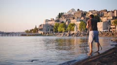 A Man Wearing Shorts Standing In The Lake Bracciano Shore With His Camera Capturing The Beauty Of Castello Orsini-Odescalchi In Rome, Italy. -wide shot