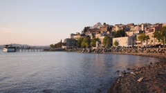 Peaceful Morning At Bracciano Lake With Birds Resting On the Rocky Shore. Overlooking The Anguillara Town In Lazio, Rome, Italy.- wide shot