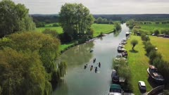 People Paddling Kayak On River Thames In Abingdon Town, Oxford City, UK During Summertime. - aerial drone shot