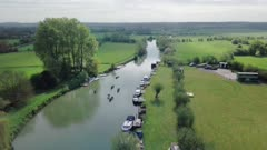 Kayak and canoe outdoors water sports Adventure In River Thames With Calm Waters Surrounded By Lush Green Fields In Oxford, England - Drone Shot Tilting Down