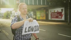 With a soft golden sunsetting glow surrounding him, a red-headed man holds up a sign hitchhiking to Central London.