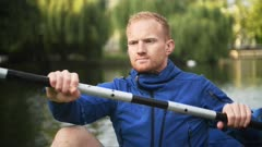 Close up of kayaker with serious face paddling in London canal, slow motion