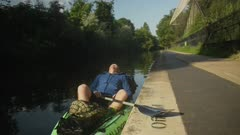 An adult man rests on the side of a river in his green kayak taking a moment to breathe in thoughtful meditation and appreciation of the calm moment.