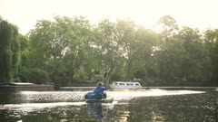 Man in kayak paddles down London city canal in golden hour sunlight
