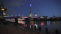 London skyline with lights at night on the River Thames beach at low tide looking at the Shard, shot in Coronavirus Covid-19 lockdown