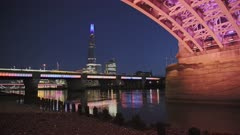 London city skyline with lights lit up at night on the River Thames beach at low tide looking at the Shard, under Southwark Bridge, shot in Coronavirus Covid-19 lockdown