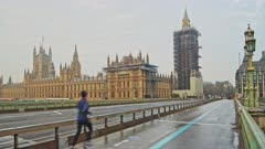 Empty quiet roads in London in Coronavirus Covid-19 lockdown at Westminster Bridge with Houses of Parliament and Big Ben and one person running, jogging in England, UK