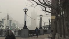 One person walking with bicycle at Tower Bridge in London on the first morning of the Coronavirus Covid-19 lockdown in the atmospheric moody misty weather, England, UK