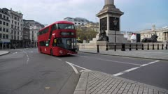 Quiet, empty streets in London with only one red London bus in Coronavirus Covid-19 pandemic lockdown at Trafalgar Square and Nelsons Column in London in the City of Westminster, England, UK