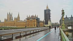 London in Coronavirus Covid-19 lockdown with empty roads and streets with no cars or traffic at Westminster Bridge with Houses of Parliament, Big Ben and people walking in England, UK at rush hour