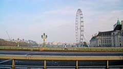 Quiet and empty roads at rush hour in London in Coronavirus Covid-19 lockdown with deserted streets at Westminster Bridge and London Eye, no traffic or cars and people walking at rush hour