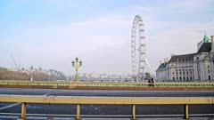 Quiet and empty roads at rush hour in London in Coronavirus Covid-19 lockdown with deserted streets at Westminster Bridge and London Eye, no traffic or cars and people walking for commuting