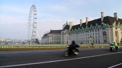 Police convoy of motorbikes in London in Coronavirus Covid-19 lockdown with quiet empty and deserted roads and streets at Westminster Bridge and London Eye in England, UK