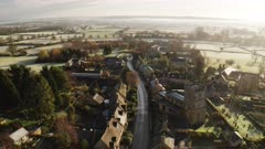 Aerial drone video of a Cotswolds Village, English countryside fields and scenery with houses, property and real estate in the UK housing market, Bourton on the Hill, Gloucestershire, England