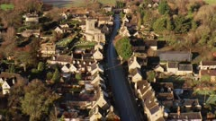 Aerial drone video of a Cotswolds Village, a rural scene in English countryside with houses, property and real estate in the UK housing market, Bourton on the Hill, Gloucestershire, England