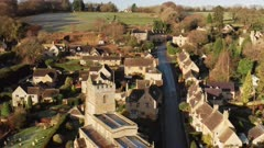 Aerial drone video of a quiet empty roads during Coronavirus Covid 19 pandemic lockdown in a Cotswolds Village in England, English rural scene with countryside, Gloucestershire