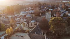 Aerial drone video of Typical English village and beautiful British countryside scenery in The Cotswolds showing a rural church at sunrise in morning sunlight at Longborough, Gloucestershire, England, UK