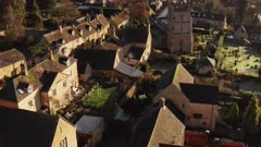 Aerial drone video of a Cotswolds Village Church, a rural scene in English countryside with houses, property and real estate in the UK housing market, Bourton on the Hill, Gloucestershire, England