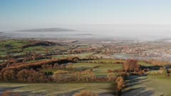 Aerial drone view of The Cotswolds Hills with Broadway in the valley, with beautiful rural countryside views, misty green fields and English landscape scenery in mist in Gloucestershire, England, UK