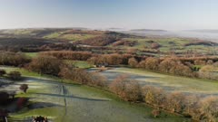Aerial drone video of Broadway Tower, a famous iconic tourist attraction in The Cotswolds Hills, iconic English landmark with beautiful British countryside scenery in mist, Gloucestershire, England, UK