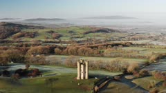 Aerial drone video of Broadway Tower, a famous iconic tourist attraction in The Cotswolds Hills, iconic English landmark with beautiful misty British countryside scenery, Gloucestershire, England, UK