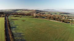 Aerial drone video of Broadway Tower, a famous old building landmark in The Cotswolds Hills, iconic English tourist attraction in beautiful British countryside with green fields, Gloucestershire, England, UK