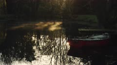 Rowing boat at a pier with mist moving on a lake in a magical peaceful calm atmospheric countryside scene in a beautiful garden, English countryside scene of lakes and trees, England