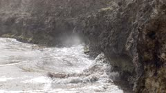 Slow Motion shot of waves crashing onto rocks; camera pans over to Caribbean Martin nests in the rocks