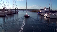 Following Sailboat Motoring Out Of Marina