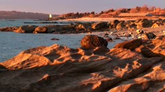 Rocks In Sunset Light On Shoreline, Lighthouse In Background