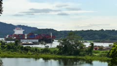 Cargo ship sailling through the Panama Canal with jungle and mountains