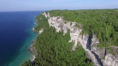 Aerial rising shot of Lion's Head dramatic cliffs above clear blue water