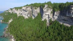 Drone flying away from dramatic Canadian high cliffs covered in trees