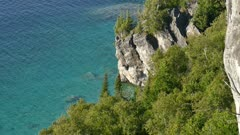 Pine trees grow among large stone falling into clear turquoise water