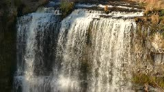Top of waterfall lit by sun with moderate water flow in natural setting