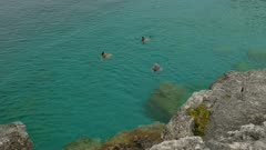 Trio of people swim in clear waters of the Bruce Peninsula in Canada