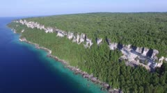 Drone back flying and rising in altitude to expose beautiful natural cliffs