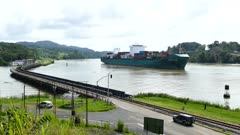 Cargo ship sailling slowly through Panama Canal with small bridge
