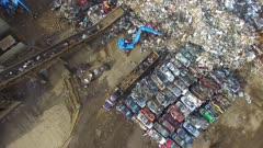 Car crushing cranes putting debris on conveyor belt