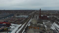 Drone flying around abandonned building in winter near railroad
