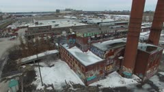 Slow left to right drone shot of industrial buliding full of graffiti