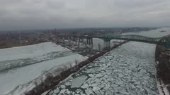 Drone flying above icy waters and near cranes building a bridge