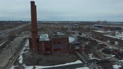 Drone rising and flying around deserted factory in North America