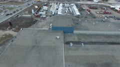 Drone camera revealing old factory with cranes in background