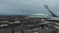 Drone gliding sideways towards large Montreal arena complex