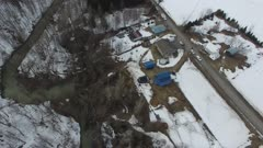 Aerial view moving above site of landslide threatening homes