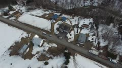 Drone flying above houses on rural road with landslide in backyard